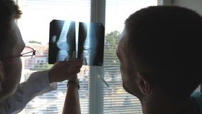 Medische arbeiders in ziekenhuis die en x-ray drukken het analizing eruit zien De dokter raadpleegt elkaar Mri van de twee mannel stock footage