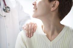 Medische arts die hogere patiënt geruststellen en een hand op patient'sschouder zetten stock fotografie