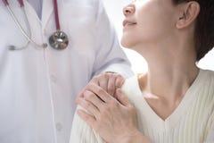 Medische arts die hogere patiënt geruststelt en een hand op patient'sschouder zet stock foto