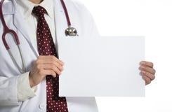 Medische arts die wit leeg document houden die de voorzijde op witte achtergrond onder ogen zien stock afbeelding