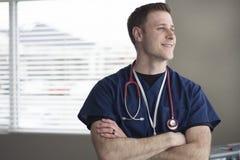 Medische arts die zich met stethoscoop in bureau bevinden Stock Afbeelding
