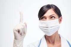 Medische arts in masker dat vinger benadrukt Stock Afbeelding