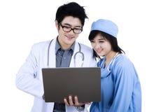 Medische artsen die computer met behulp van royalty-vrije stock afbeeldingen