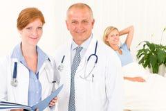 Medische artsen met het ziekenhuispatiënt het liggen bed Stock Foto's