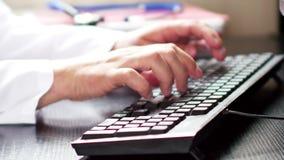 Medische artsenhanden die op computertoetsenbord typen stock footage