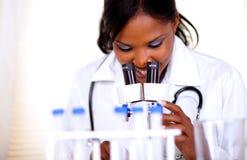 Medische artsenvrouw die met een microscoop werkt Stock Foto