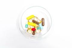 Medische capsules binnen glas Stock Afbeelding