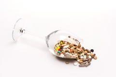 Medische capsules en tabletten binnen wijnglas Stock Afbeelding