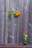 Medische kruidenbos op muur en vaas met bloemen stock afbeelding