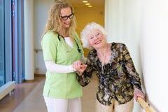 Medische Medewerker die Gelukkige Bejaarde Patiënt bijstaan Royalty-vrije Stock Foto
