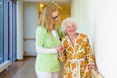 Medische Medewerker die het Gelukkige Oude Vrouw Lopen bevorderen stock foto