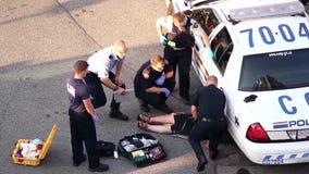 Medische mensen en politie die de hartaanvalmens helpen stock footage