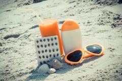 Medische pillen, wortelsap en toebehoren voor het zonnebaden bij strand, vitamine A en mooie, duurzame tan royalty-vrije stock fotografie