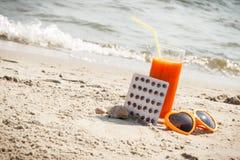 Medische pillen, wortelsap en zonnebril op zand, vitamine A en mooie, duurzame tan stock fotografie