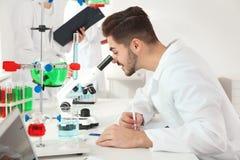 Medische student die met microscoop in wetenschappelijk laboratorium werken royalty-vrije stock foto