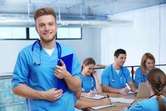 Medische student met groupmates in bibliotheek stock afbeeldingen