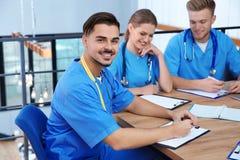 Medische student met groupmates in bibliotheek stock foto