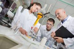 Medische studenten die met microscoop bij universiteit werken stock foto's