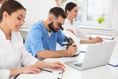 Medische studenten die in moderne wetenschappelijk werken stock foto's