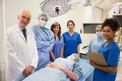 Medische studenten en professor die bij camera glimlachen Stock Foto's