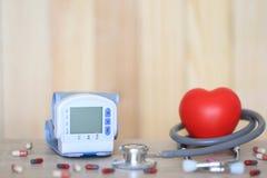 Medische tonometer voor het meten van bloeddruk met stethoscoop en rood hart op wooderachtergrond, Medische kost en Gezondheid stock foto's