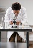 Medische wetenschapper die door microscoop kijkt Royalty-vrije Stock Afbeeldingen