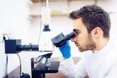 Medische wetenschapper die met microscoop, steekproeven en vloeistof in laboratorium onderzoeken royalty-vrije stock fotografie