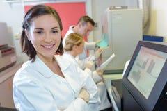 Medische wetenschappers die digitale machines met behulp van bij laboratorium royalty-vrije stock foto's