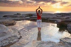 Meditação da ioga da mulher pelo nascer do sol do oceano fotografia de stock
