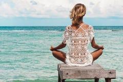 Meditação da mulher em uma pose da ioga na praia fotografia de stock royalty free