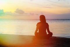 Meditação da mulher na praia imagens de stock