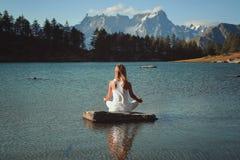 Meditação da mulher no lago da montanha fotografia de stock royalty free