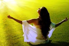 Meditação em um campo em feixes solares Imagens de Stock Royalty Free