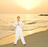Meditação em um nascer do sol por um mar Imagens de Stock Royalty Free