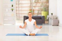 Meditação envelhecida meio da mulher foto de stock