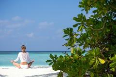 Meditação praticando da ioga da jovem mulher na praia que enfrenta o oceano perto de uma palmeira em Maldivas Imagens de Stock Royalty Free