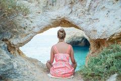 Meditação praticando da jovem mulher durante o por do sol sob uma formação natural do arco da pedra calcária por Algarves, Portug fotografia de stock royalty free