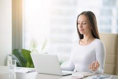 Meditação praticando da jovem mulher na mesa de escritório
