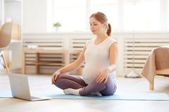 Meditación casera practicante de la mujer embarazada fotografía de archivo