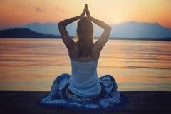 Meditación de la mujer en la hora de la puesta del sol Imágenes de archivo libres de regalías