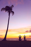 Meditación de la yoga - siluetas de la gente en la puesta del sol Imagenes de archivo