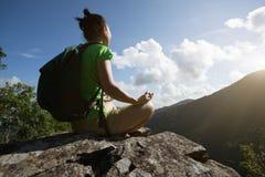 Meditación del caminante de la mujer en el borde del acantilado del top de la montaña foto de archivo