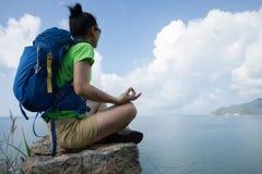 Meditación del caminante de la mujer en el borde del acantilado del top de la montaña imagen de archivo libre de regalías