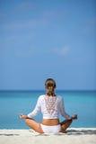 meditación Foto de una mujer que se está sentando en la posición de loto respecto a la costa Maldivas del océano Foto de archivo libre de regalías