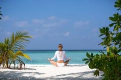 Meditación hermosa joven de la mujer en la playa Maldivas Fotografía de archivo libre de regalías