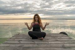 Meditación practicante sonriente de la mujer en la posición de la yoga del loto respecto a un embarcadero de madera imagenes de archivo