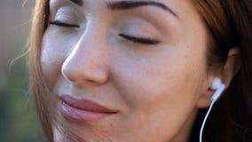 meditación Relájese El primer de la mujer en los auriculares que sonreían y la música que escuchaba con ella los ojos cerraron al metrajes