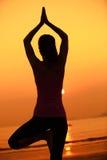 Meditación sana de la mujer de la yoga en la playa de la salida del sol Imágenes de archivo libres de regalías