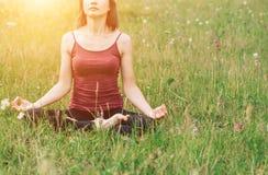 Meditación y yoga en el campo Mujer hermosa en una sentada superior de Borgoña en la hierba en el sol foto de archivo libre de regalías