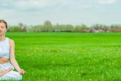 meditaci?n Mujer que hace yoga y que escucha para relajar m?sica imagen de archivo